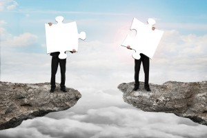 Businessmen holding jigsaw puzzles to connect on cliff with clou
