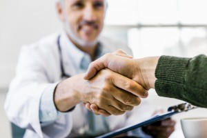 Doctor shaking hands with patient in clinic