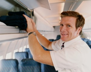 Male Flight Attendant Placing Objects in an Over Head Locker on a Plane