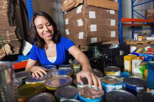 Young mixed-race woman sorting donated groceries in food bank warehouse